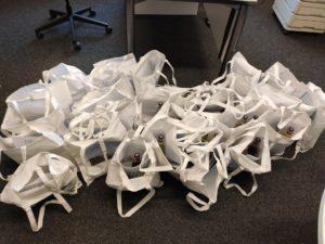 30 Projekttaschen für die Teilnehmer der Fahrt und die Projekträger. Die Taschen sind befüllt mit der Broschüre, Ablaufplan, Bionadeflaschen, Notizblock, Stift und Ansichtskarte. Foto: Kokula)