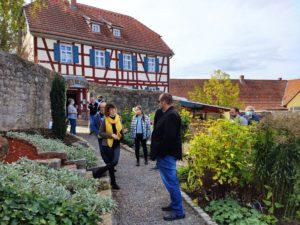 Frau Kupfer (gelber Schal) ging auf die religiöse Bedeutung der Pflanzen und den gemeinschaftlichen Treffpunkt für die Gemeinde Sondheim/Rhön ein. Der Bibelgarten steht allen Konfessionen jeder Zeit offen (Foto: Kokula).